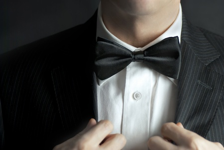 A close-up shot of a man straightening his tux. Stock Photo