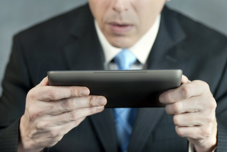 A close-up shot of a businessman looking at a tablet computer with concern. photo