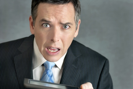 A close-up shot of a businessman looking to camera confused by his tablet computer.