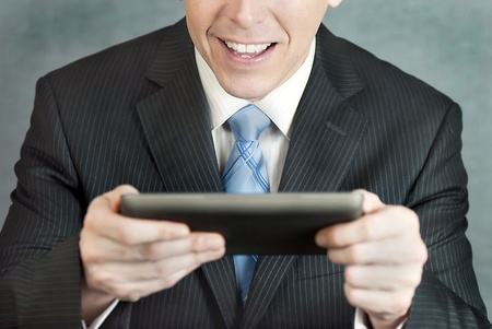 A close-up shot of a businessman looking at a tablet computer with excitement. photo