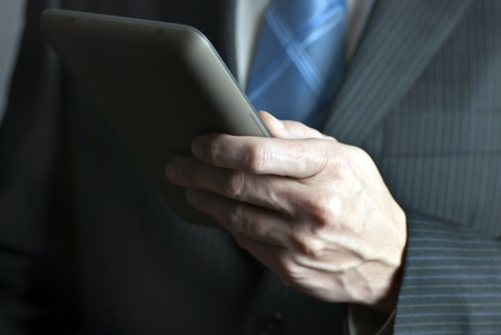 A close-up shot of a businessman holding a tablet computer. photo