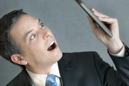 A close-up shot of a businessman looking at a tablet computer with awe. photo