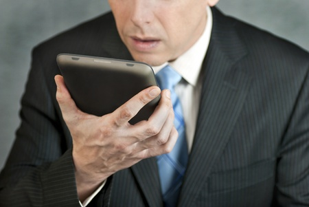 A close-up shot of a businessman looking at a tablet computer with despair. Stock Photo - 9009448