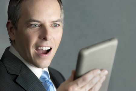 A close-up shot of a confident businessman looking at a tablet computer with pleased surprise. photo