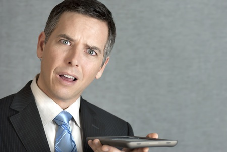 A close-up shot of a businessman perplexed by his tablet computer. photo