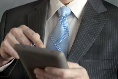 A close-up shot of a businesman using a tablet computer. photo