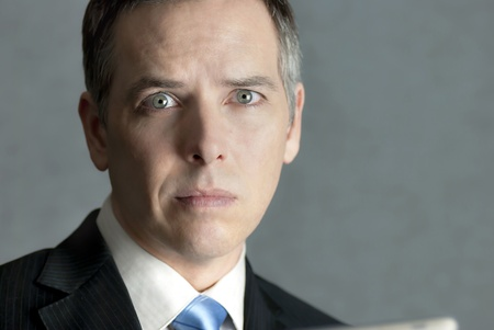 A close-up shot of a businessman looking at the camera with concern. photo