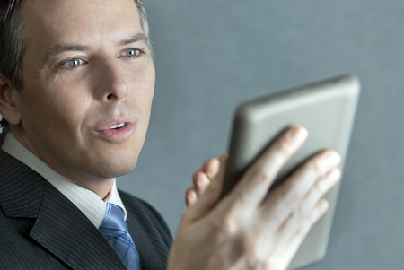 A close-up shot of a confident businessman gesturing to his tablet computer.