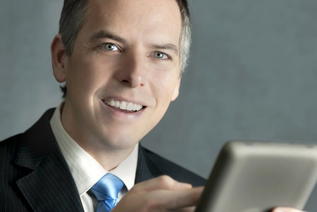 A close-up shot of a confident businessman looking to camera while using his tablet computer. photo