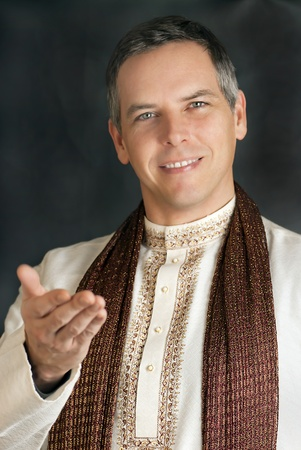 A close-up shot of a peaceful man in traditional Indian clothing gesturing to camera.