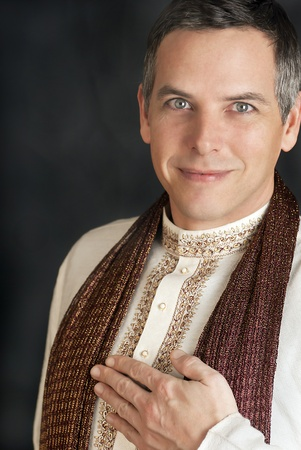 kurta: A close-up shot of a peaceful man in traditional Indian clothing with his hand to his chest.