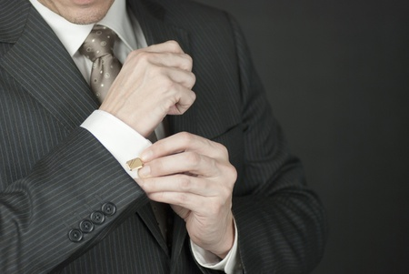 necktie: Close-up of a businesman adjusting his cufflink.