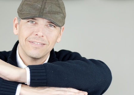 newsboy cap: Close-up of a smiling confident man in a newsboy hat looking to camera resting his arms on a chair back.