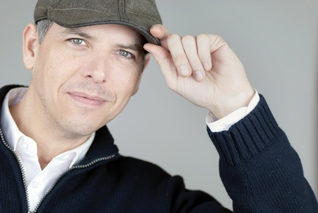 newsboy cap: Close-up of a smiling confident man tipping his newsboy hat to camera.