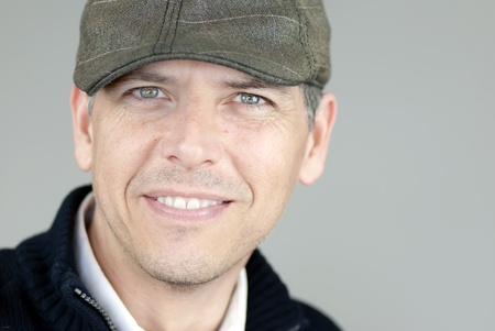 newsboy cap: Close-up of a smiling man in a newsboy hat looking to camera.