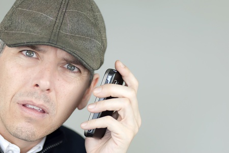 depress: Close-up of a stressed man in a newsboy hat talking on his cell phone.