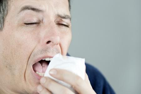 persona deprimida: Primer plano de un hombre estornudos. Foto de archivo