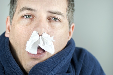 Close-up of a man with tissue in his nose. 版權商用圖片