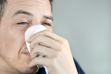 Close-up of a man holding a  tissue on his nose. photo