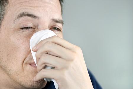 persona triste: Primer plano de un hombre sosteniendo un tejido en su nariz.