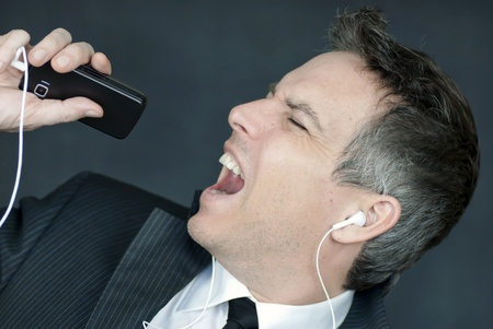 Close-up of a businessman wearing headohones singing into his cell phone. photo