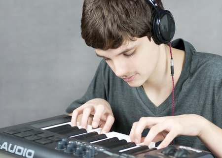 Close-up of a focused teen playing his keyboard. photo