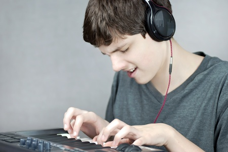 Close-up of a headphone wearing teen playing his keyboard. Stock Photo - 9328596
