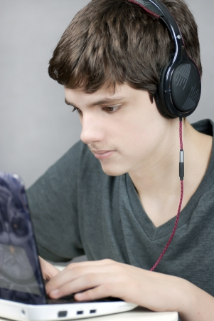 Close-up of a teen wearing headphones working on his netbook. Stock Photo