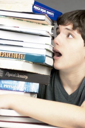 Close-up of a terrified teen looking at a stack of textbooks. Stock Photo