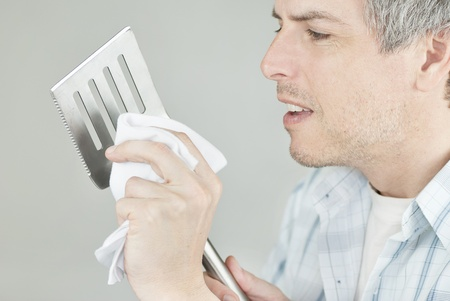 Close-up of a man polishing his BBQ flipping spatula. photo
