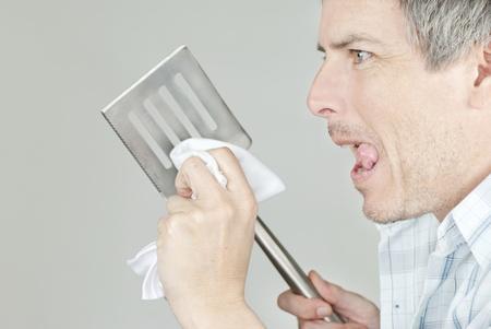 Close-up of a man polishing his BBQ flipping spatula photo