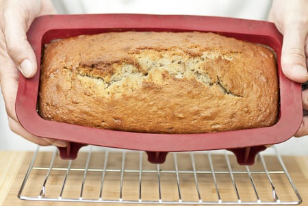 Close-up of a chef displaying banana bread fresh out of the oven. photo