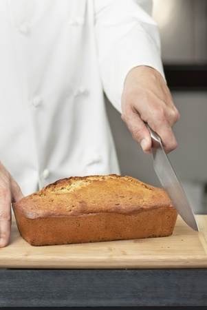 Close-up of a chef starting to slice banana bread on a bamboo cutting board. Stock Photo - 9585231