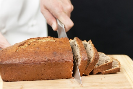 Close-up of a chef slicing banana bread on a bamboo cutting board. Stock Photo - 9585267