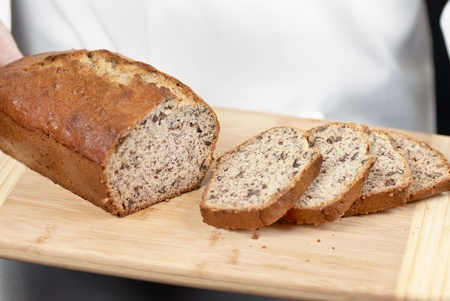 Close-up of sliced banana bread with a chef standing in the background. photo