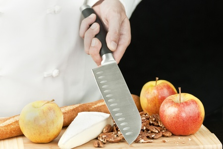 Close-up of a chef holding a knife over a bamboo cutting board of apples, brie, a baguette and pecans. photo