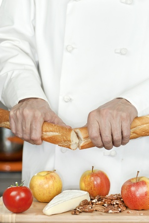 Close-up of a chef breaking a baguette over a cutting board of apples, pecans, a tomato and brie. photo