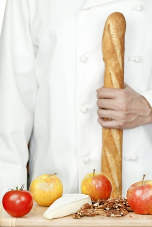 Close-up of a chef holding a baguete in front of a bamboo cutting board of apples, brie and pecans. photo