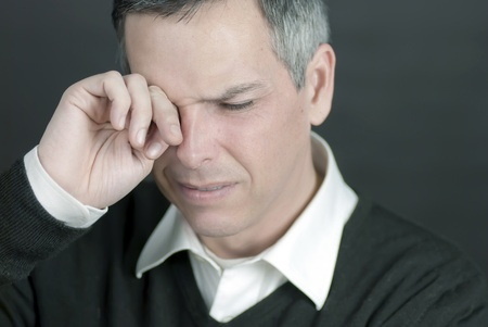Close-up of a man with a migraine rubbing his eyes. photo