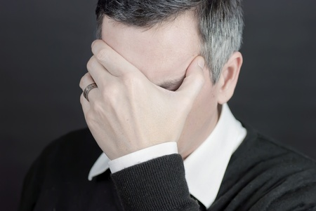 Close-up of a man with a migraine covering his eyes.