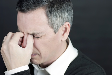 Close-up of a man with a migraine holding the bridge of his nose. Stock Photo