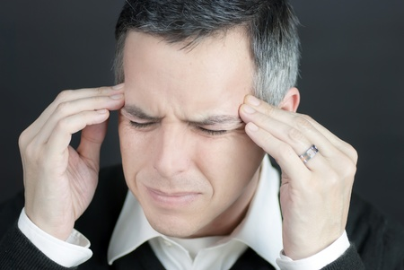 Close-up of a man with a migraine holding his temples. photo