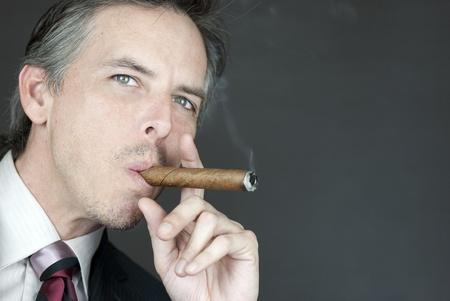 Close-up of a confident businessman smoking a cigar, side view. photo