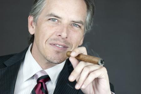 Close-up of a successful businessman smoking a cigar. photo