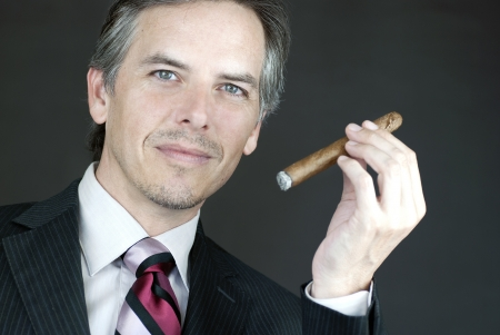 Close-up of an elegant businessman holding a cigar.
