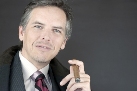 Close-up of a successful businessman holding a cigar.