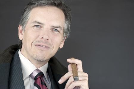 Close-up of a successful businessman holding a cigar.