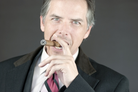 cigar smoking man: Primer plano de un empresario seguro de fumar un cigarro.