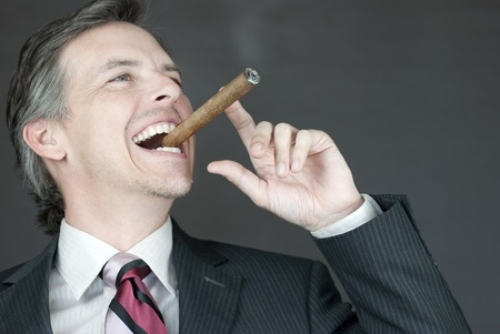 cigar smoking man: Close-up of a businessman celebrating with a cigar, side view.