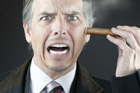 Close-up of a stressed businessman stubbing out his cigar on his face.